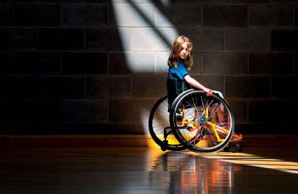 dziewczynka siedzi na wózku inwalidzkim i patrzy się w naszą stronę